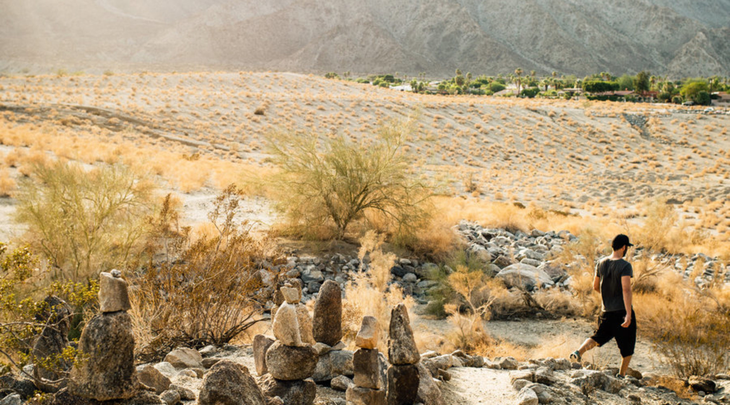 Man taking one of the best hikes in La Quinta, La Quinta Cove, through rocks and open meadows