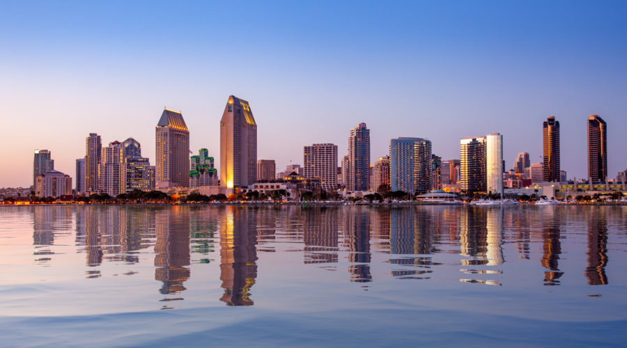 Sunset illuminating the tall skyscrapers of San Diego, one of the best places to live in California. Photographed from Centennial Park in Coronado with artificial water reflection