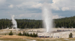 People watching Beehive Geyser erupt with Lion Geyser in Yellowstone off Highway 89