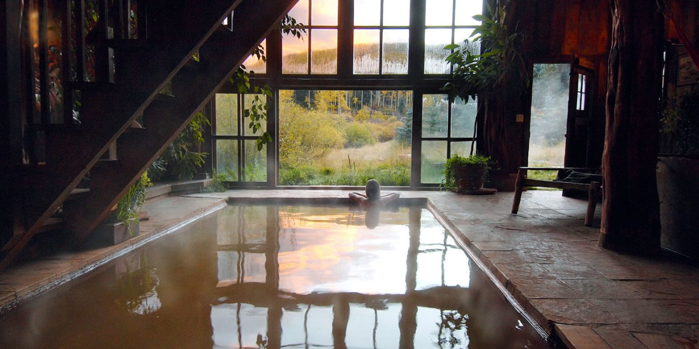 Woman soaking in the indoor hot springs pool at Dunton Hot Springs Resort