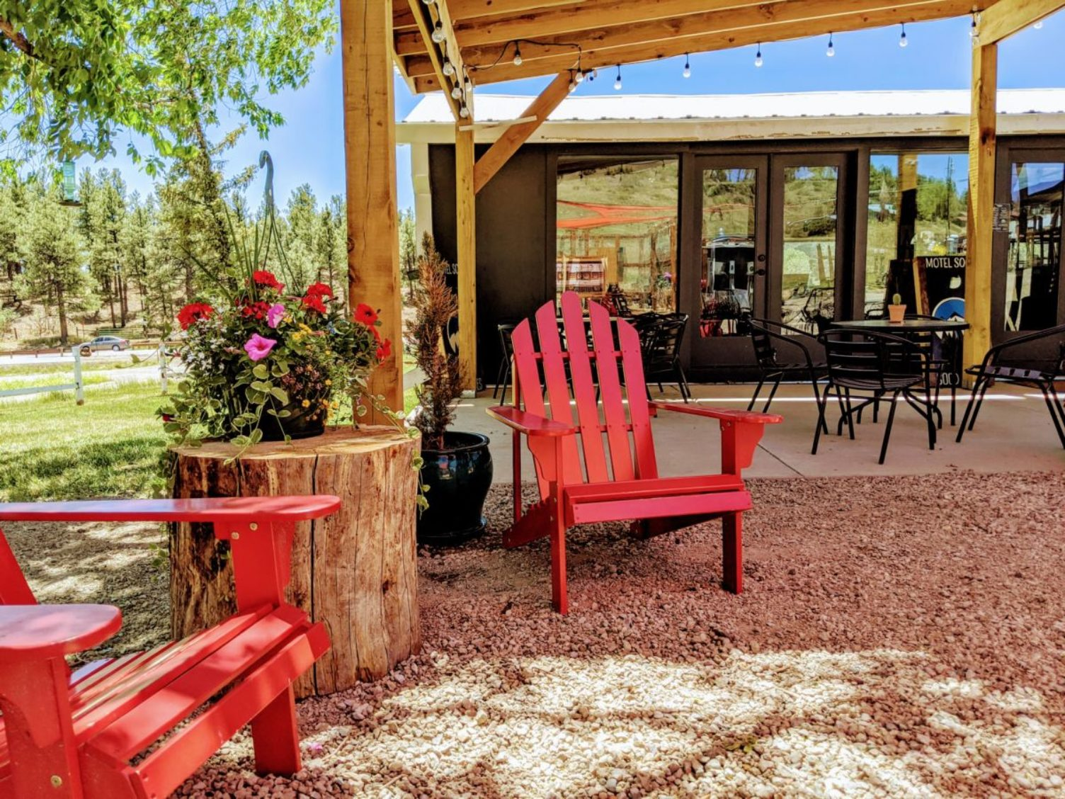 Outdoor patio at the Motel SOCO with red lawn chairs and tables in the background.
