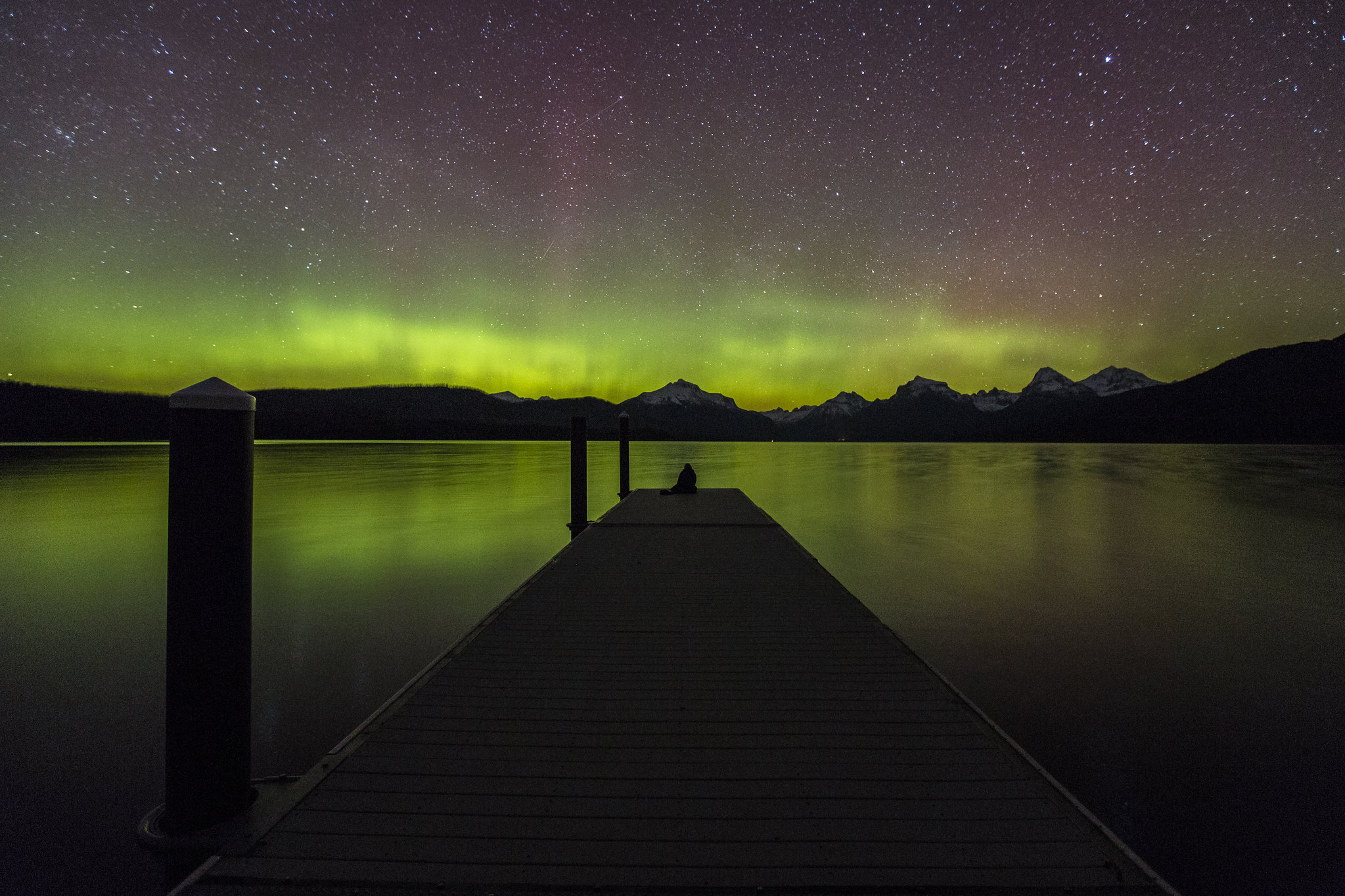 Person at end of dock watching northern lights in Glacier National Park