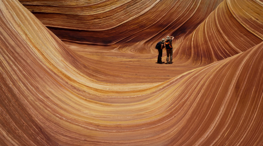 A couple photographing The Wave, a striated sandstone rock formation in Coyote Buttes