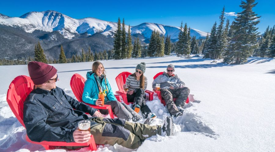 Skiers sitting in chairs in the snow drinking beer in the sun at Purgatory ski resort in Durango, CO