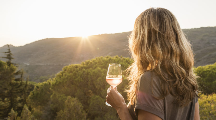Woman Holding Glass of Rose Wine at Sunset